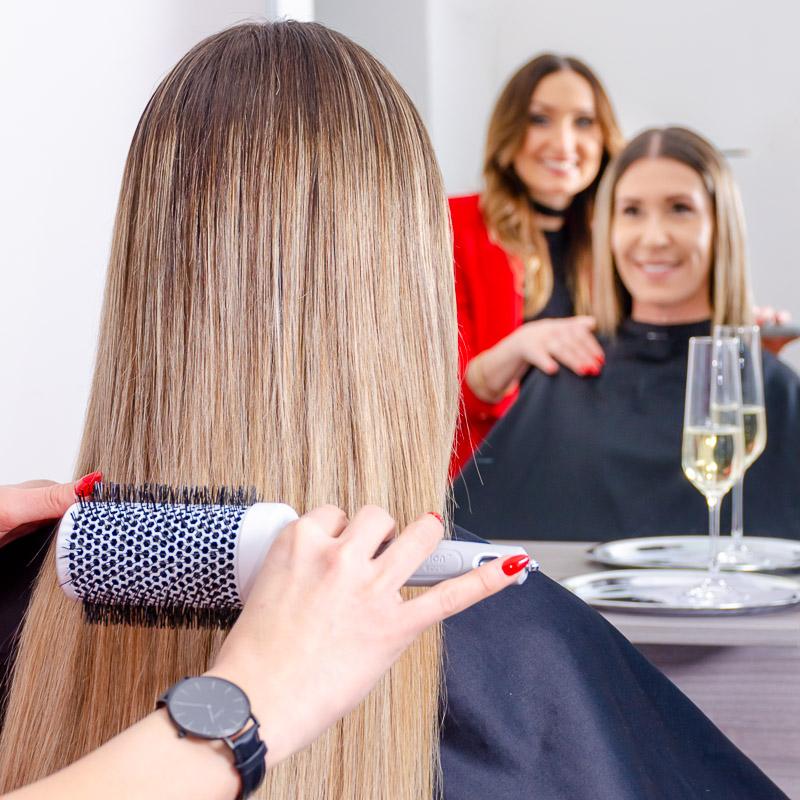 Preisliste Friseursalon: Friseurin bürstet sorgfältig die Haare Ihrer Kundin - ein umfassendes und vollendetes Wohlfühlerlebnis bei Ihrem Friseurbesuch.